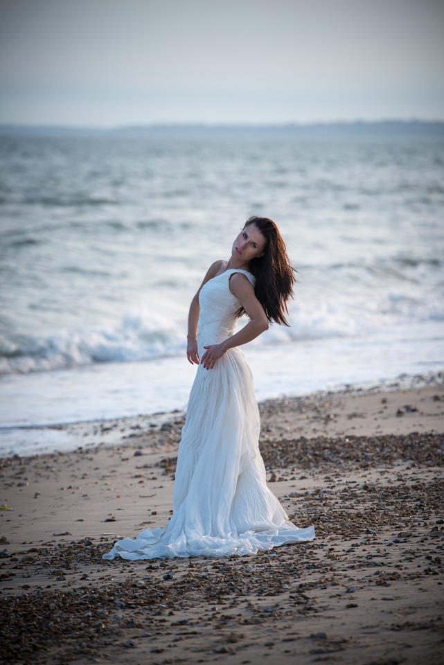 Wearing her wedding dress at the beach