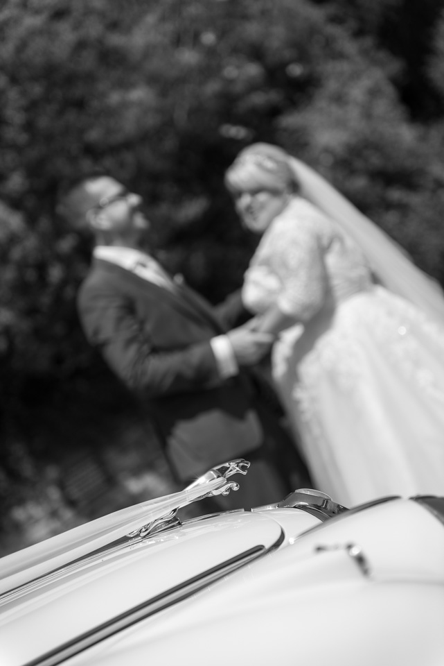 Bride, groom and wedding car