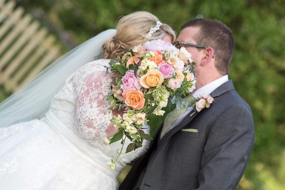 Hiding behind the bridal bouquet at their Dorset wedding