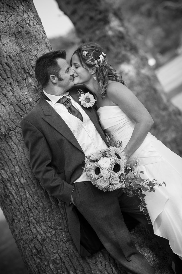 Kissing under the trees at their New Forest wedding