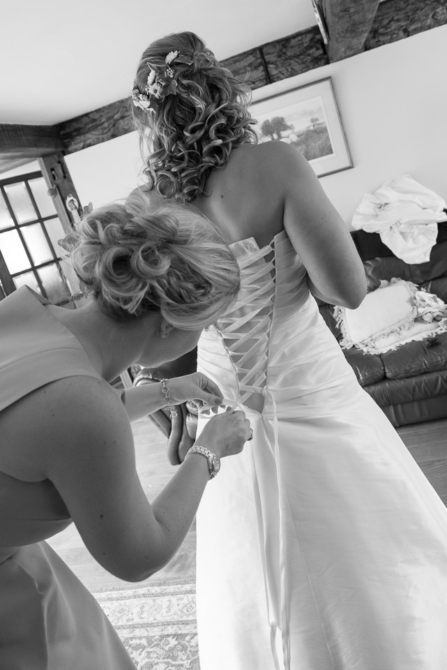 Lacing up the wedding gown during the preparations for a New Forest Wedding