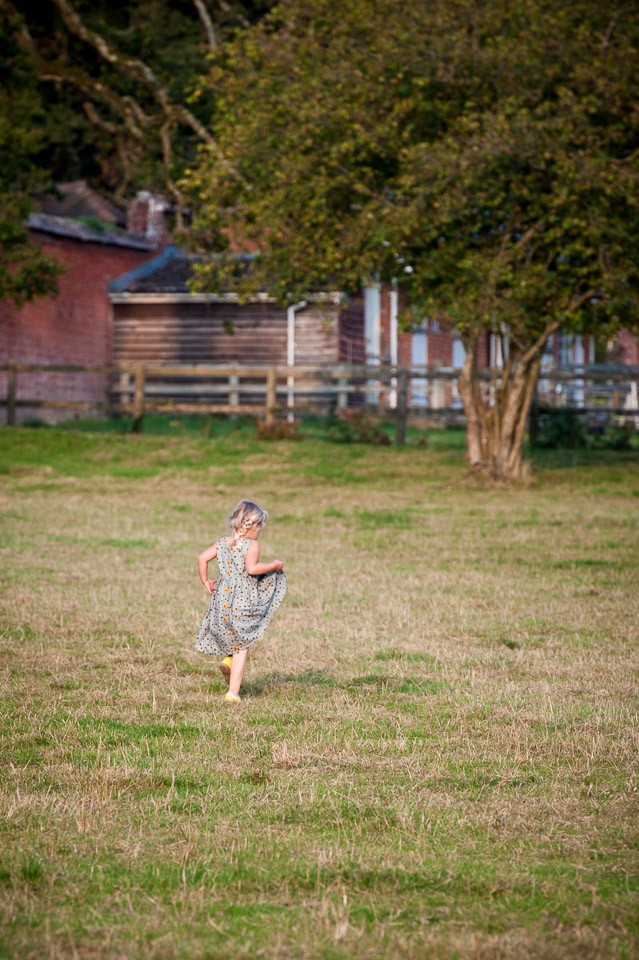 Pretty girl running across the field at New Forest wedding