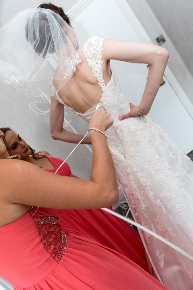 Lacing up her wedding gown