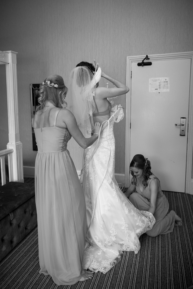 Stepping into her gown, helped by her bridesmaids